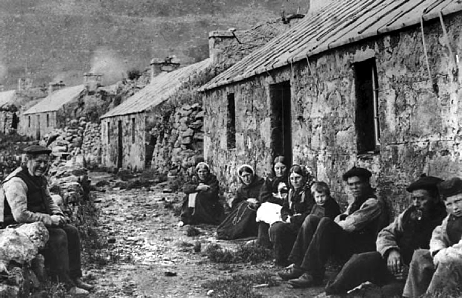 A photograph of villagers on St Kilda sitting outside their houses, taken in 1886